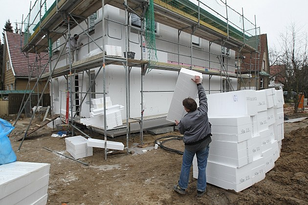 worker wrangles stryrofoam blocks for use as insulation on building construction