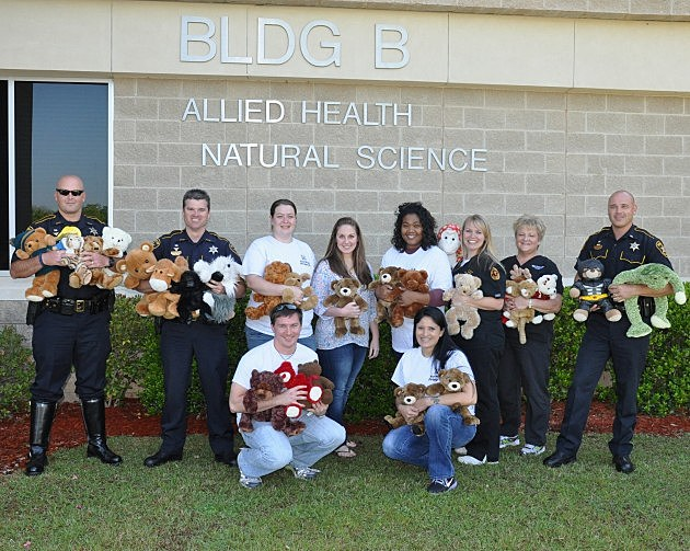 Photo of Bossier Sheriff's Deputies and BPCC nursing students pose with stuffed toys.