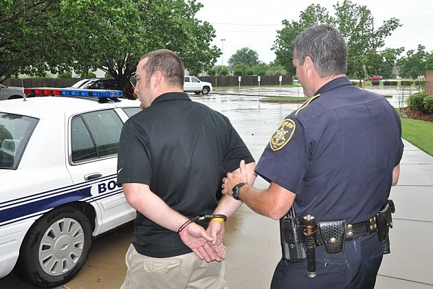 Deputy Robert Teague of the Bossier Sheriff's Office makes a mock arrest of Josh Beasley, director of Youth Ministries at Asbury Methodist Church in Bossier City.
