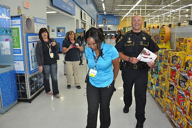 Deputy Chris Woods of the Bossier Sheriff's Office escorts Keiyetta Thomas, co-manager of Wal-Mart on Airline in Bossier City, out of the store during a mock arrest Thursday morning.