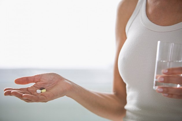 Woman holding pills