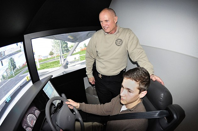 Sgt. Roff Clary shows Jacob how to use police driving simulator