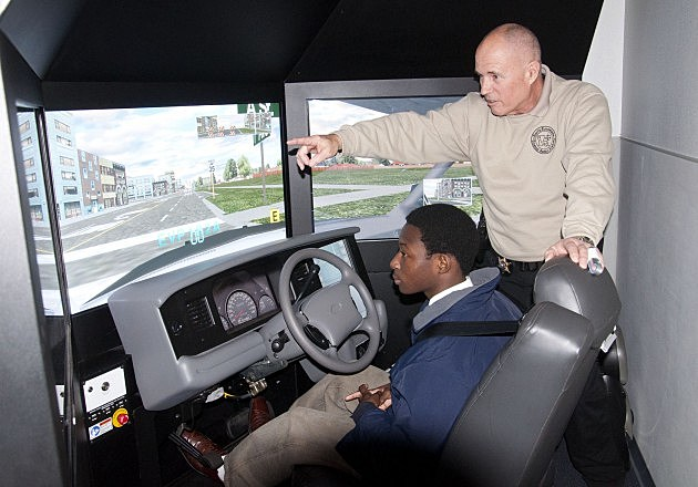 Sgt. Roff Clary shows Quinton how to use the police driving simulator